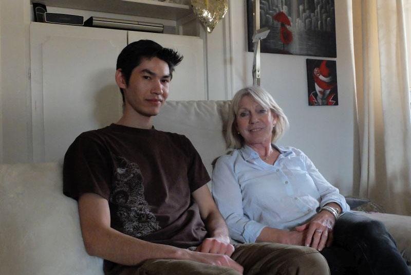 der junge Geflüchtete Yasin Rezaie und Helferin Maria el Mamar, im Hintergrund Bilder von Yasin