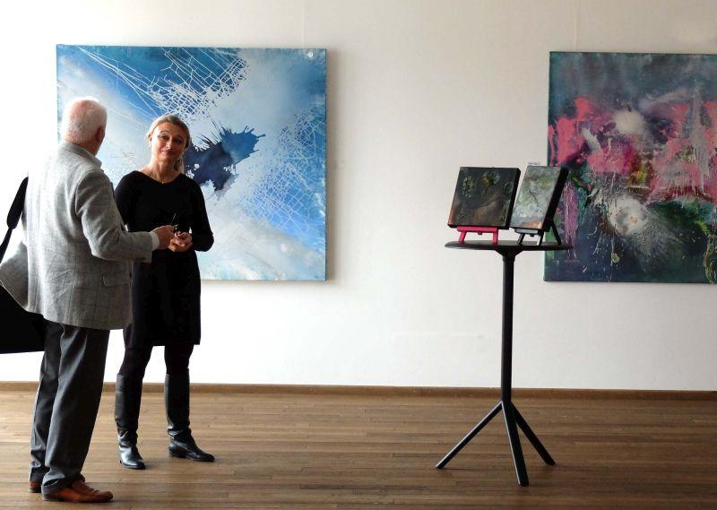 Cordula Rock im Gespräch mit einem Besucher vor den Bildern, die bei Jürgen Welker im Atelier entstanden sind