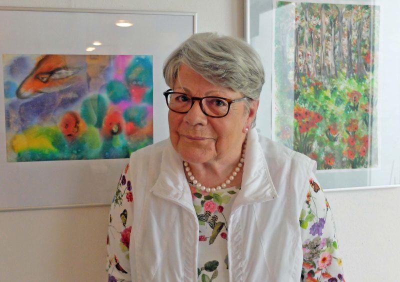 Gertrud Hoffmann vor ihren farbenfrohen Bildern.
